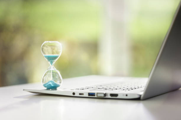 Hourglass on laptop computer concept for time management stock photo