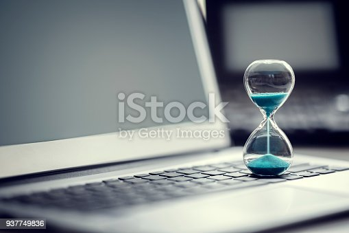 istock Hourglass on laptop computer concept for time management 937749836