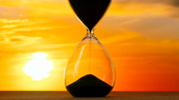Hourglass on the background of a sunset. The value of time in life. An eternity. stock photo