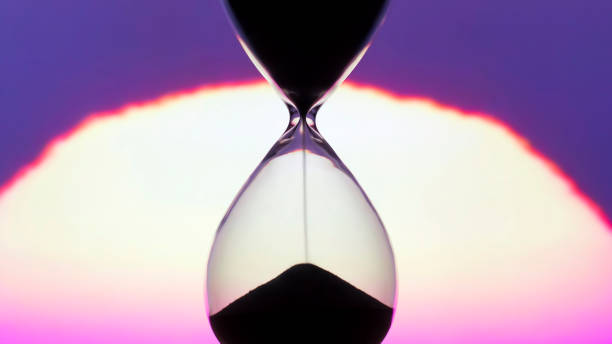 Hourglass on the background of a sunset. The value of time in life. time measuring tool. An eternity. stock photo