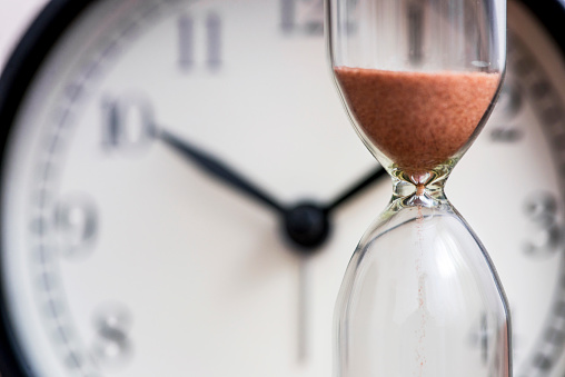 Hourglass on the background of office watch as time passing concept for business deadline, urgency and running out of time. Sand clock, business time management concept