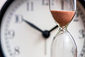 istock Hourglass on the background of office watch as time passing concept for business deadline, urgency and running out of time. Sand clock, business time management concept 1277004651
