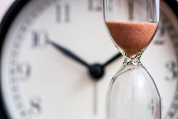 klepsydra na tle zegarka biurowego jako koncepcja czasu na termin biznesowy, pilność i wyczerpanie czasu. zegar piaskowy, koncepcja zarządzania czasem biznesowym - czas zdjęcia i obrazy z banku zdjęć