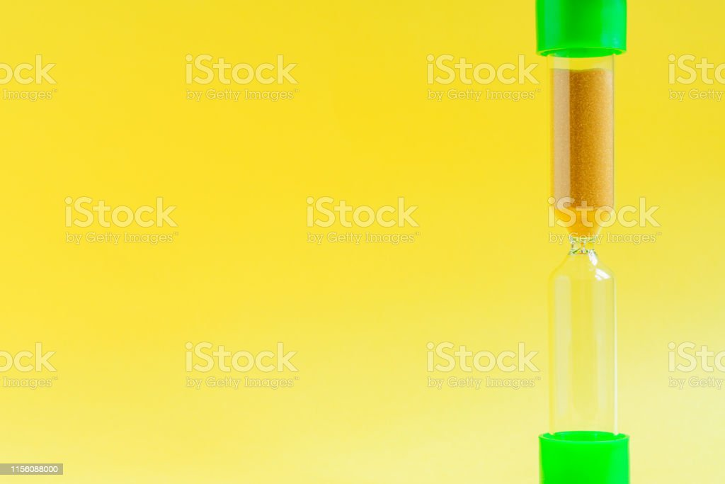 Hourglass on yellow background with copy space. Time management...