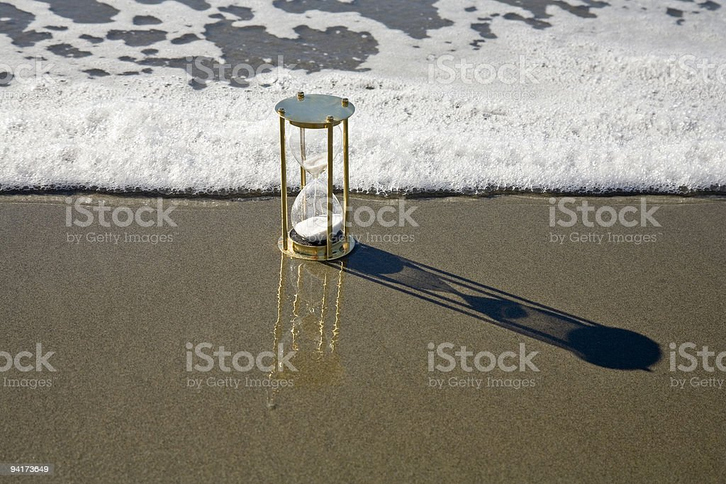 Hourglass Sand Timer and Rising Tide Surf Seashore Beach stock photo
