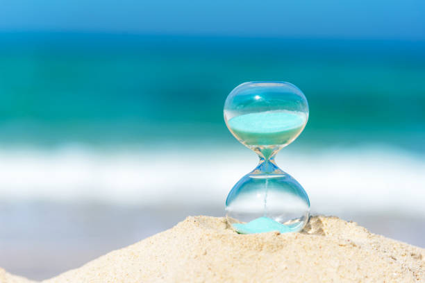 hourglass summer and vacations time on a beach in the sand  with blue sky and copy space.  lifestyle concept. - climate clock imagens e fotografias de stock