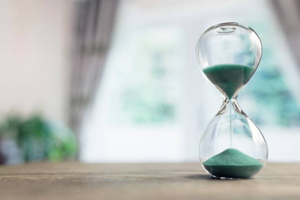 hourglass time passing in room by window - deadline stock pictures, royalty-free photos & images