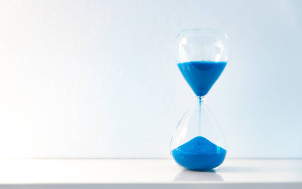 Hourglass with blue sand against a white background stock photo