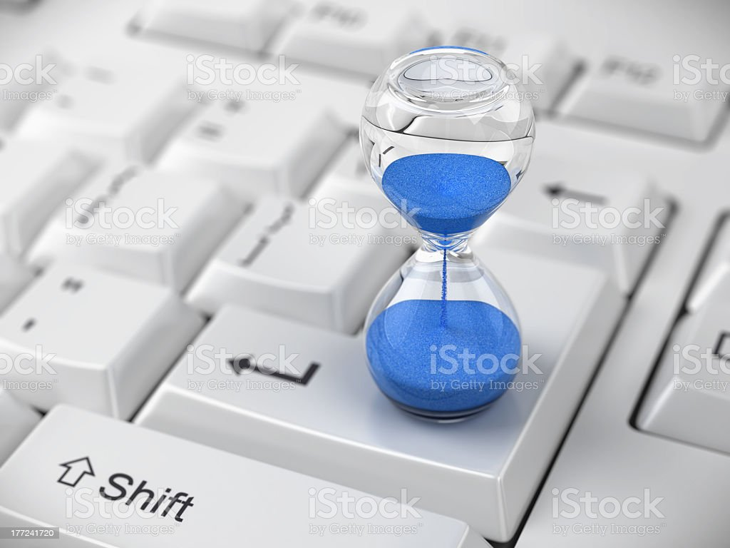 Hourglass with blue sand on enter key on computer keyboard stock photo
