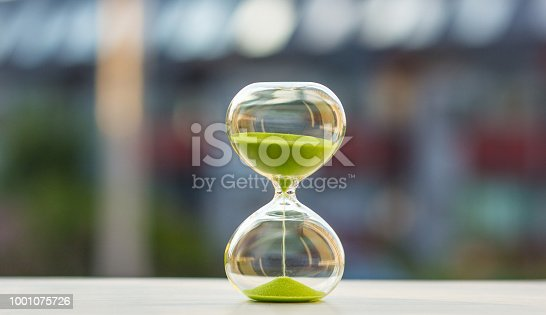 istock Hourglass with green sand on a blurred background 1001075726