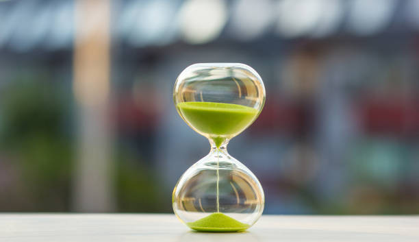 hourglass with green sand on a blurred background - deadline stock pictures, royalty-free photos & images