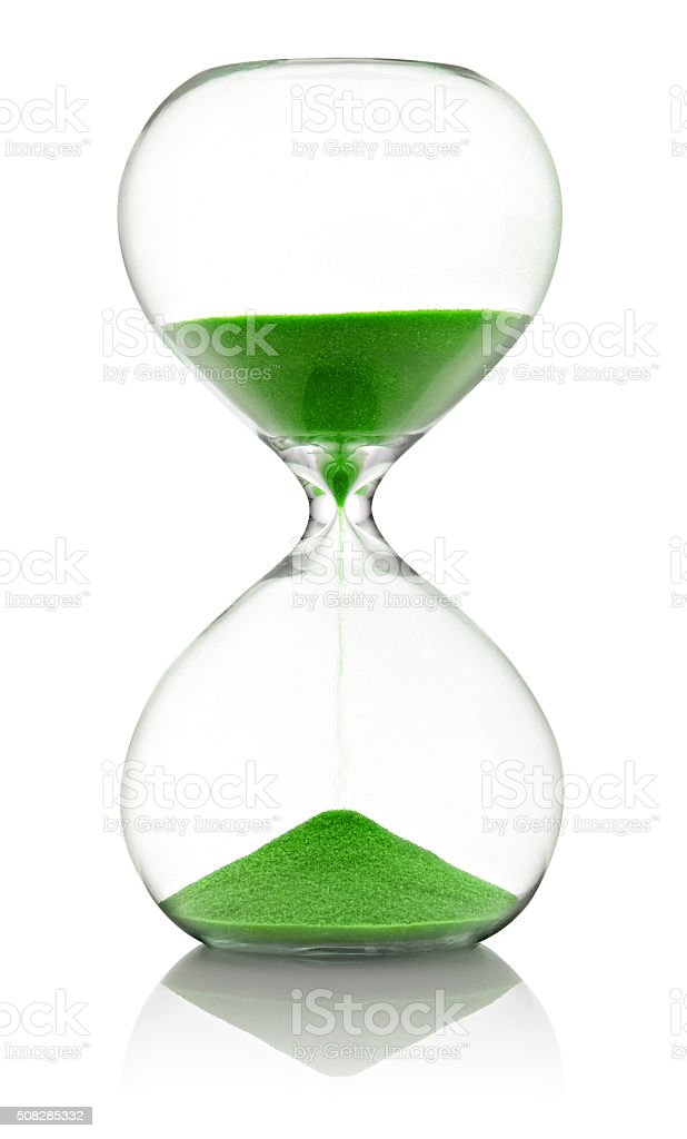 Hourglass with green sand running through stock photo