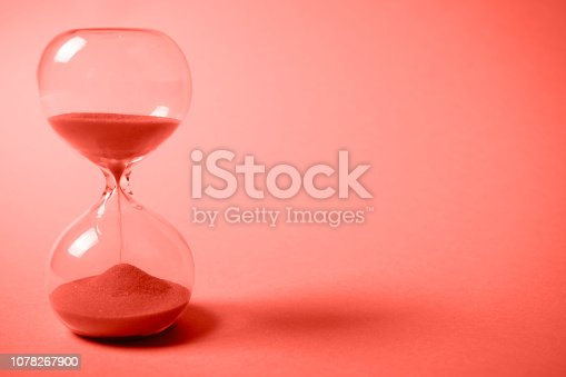 istock Hourglass with orange sand on gradient coral background. 1078267900