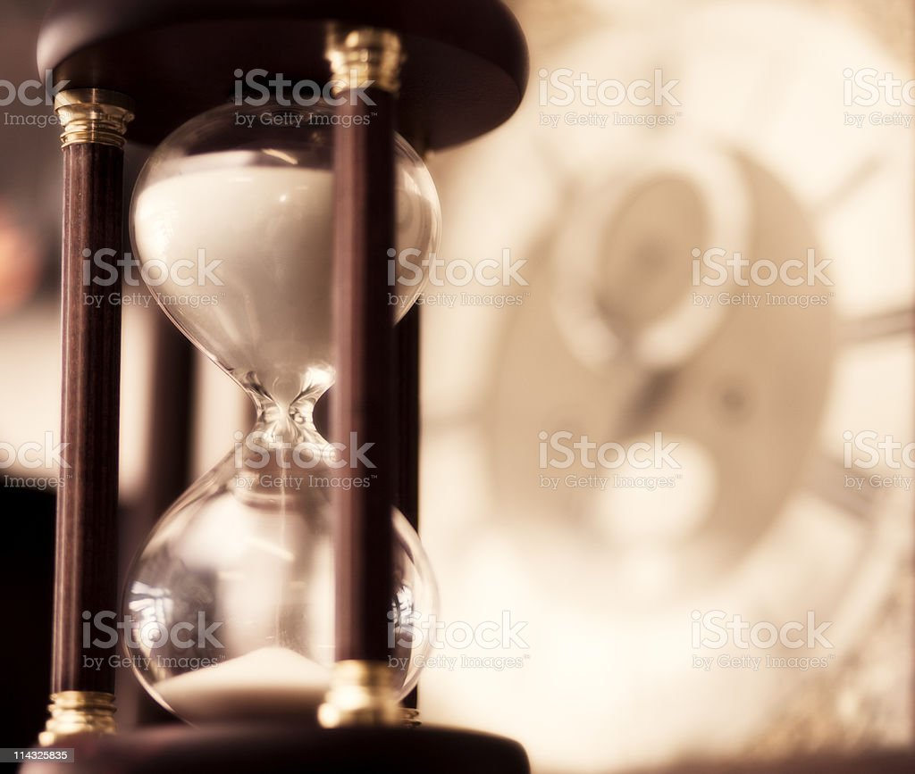 Hourglass with out of focus clockface in background, square. royalty-free stock photo