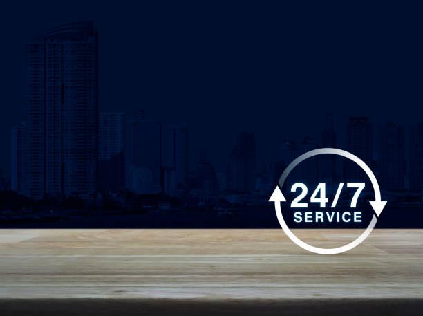 24 horas de serviço ícone na mesa de madeira sobre o fundo de torre escritório moderna cidade, conceito de serviço de tempo integral - foto de acervo