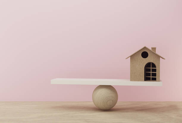 House a balance scale in equal position on wooden table and pink background. financial management, depicts short term borrowing for a residence. House a balance scale in equal position on wooden table and pink background. financial management, depicts short term borrowing for a residence. depreciation stock pictures, royalty-free photos & images