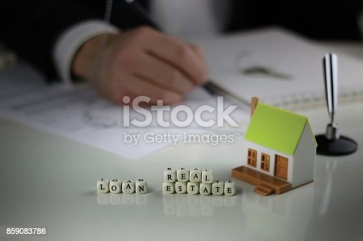 istock House Agents hands a contract loan mortgage 859083786