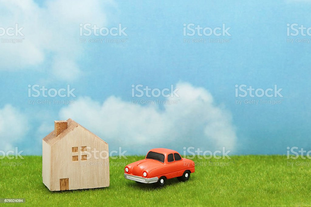 House and car on  grass over blue sky and clouds. stock photo