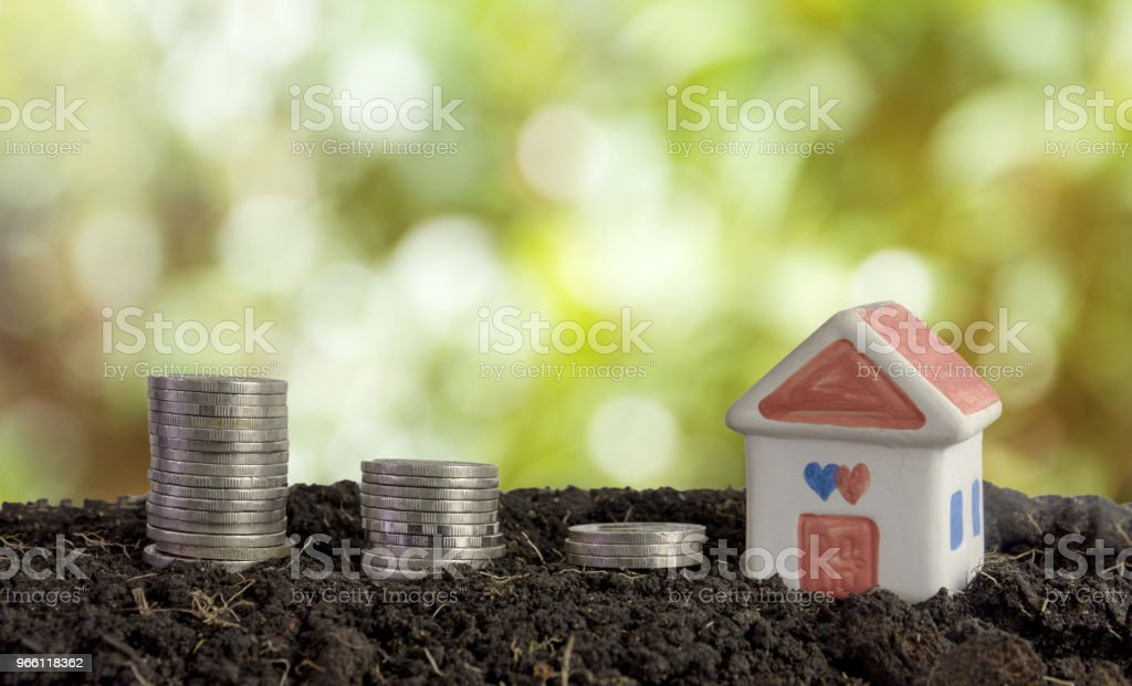 house and coins in soil, saving money to build a house concept - Royalty-free Accountancy Stock Photo