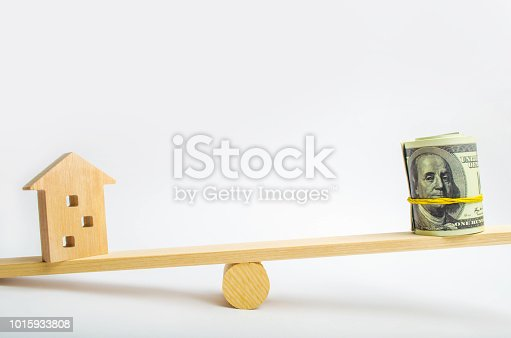 istock house and dollars on the scales. balance. buying, selling, renting a house and an apartment. credit. mortgage. property. investment in real estate. saving money. Home loan 1015933808