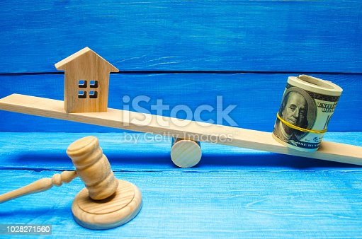 istock house and dollars on the scales. Property investment and house mortgage financial real estate concept. tax. credit. buying, selling, renting property / home. balance. court. trial. hammer of a judge 1028271560