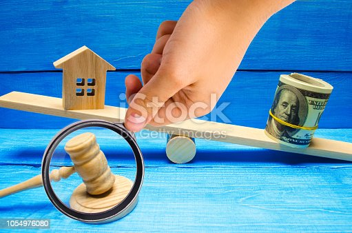 istock house and dollars on the scales. Property investment and house mortgage financial real estate concept. tax. credit. buying, selling, renting property / home. balance. court. trial. hammer of a judge 1054976080