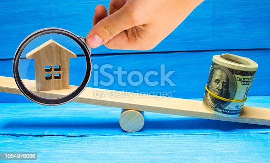 istock house and dollars on the scales. Property investment and house mortgage financial real estate concept. tax. credit. buying, selling, renting property / home. balance. court. trial. 1054976096
