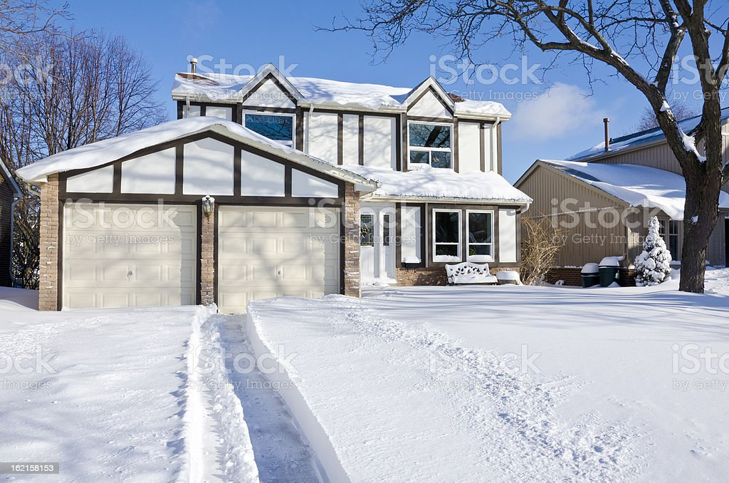 House and Driveway Covered with Fresh Snow stock photo