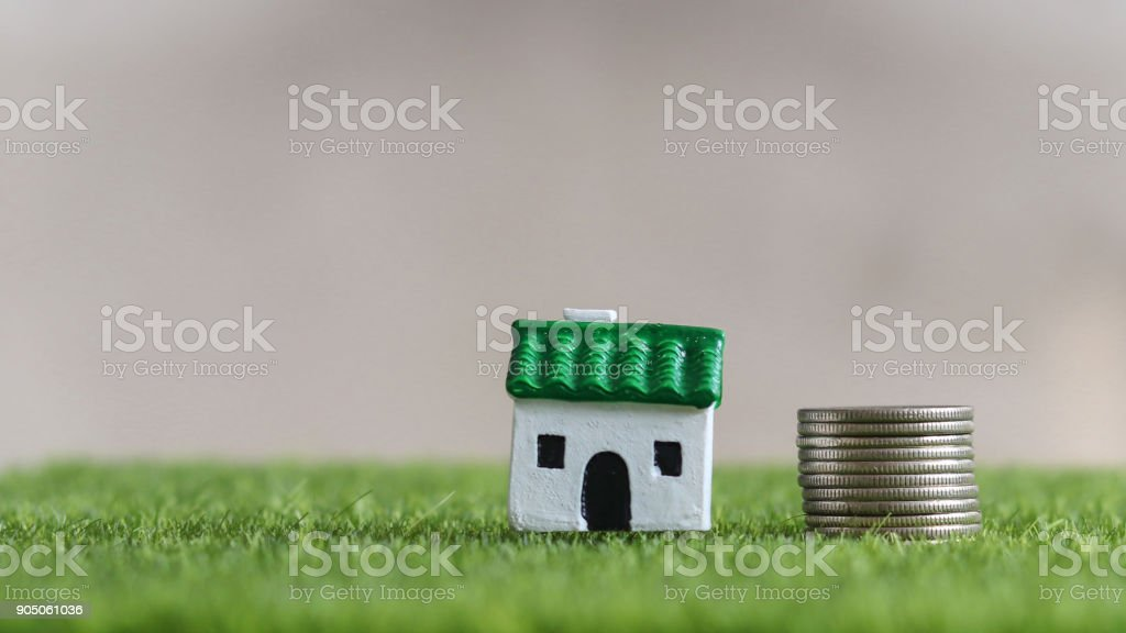 House and loan concept. Green roof miniature house and pile of coins on the lawn. stock photo