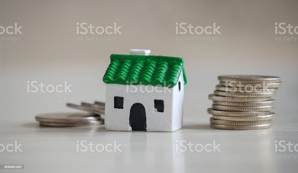 House and loan concept. Green roof miniature house and pile of coins on the soft background. stock photo