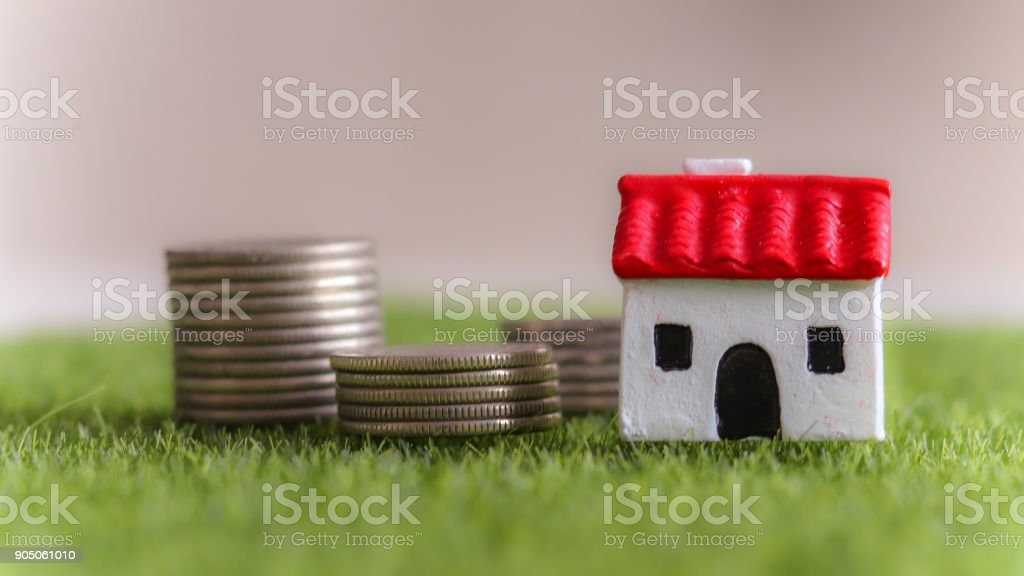 House and loan concept. Red roof miniature house and pile of coins on the lawn. stock photo