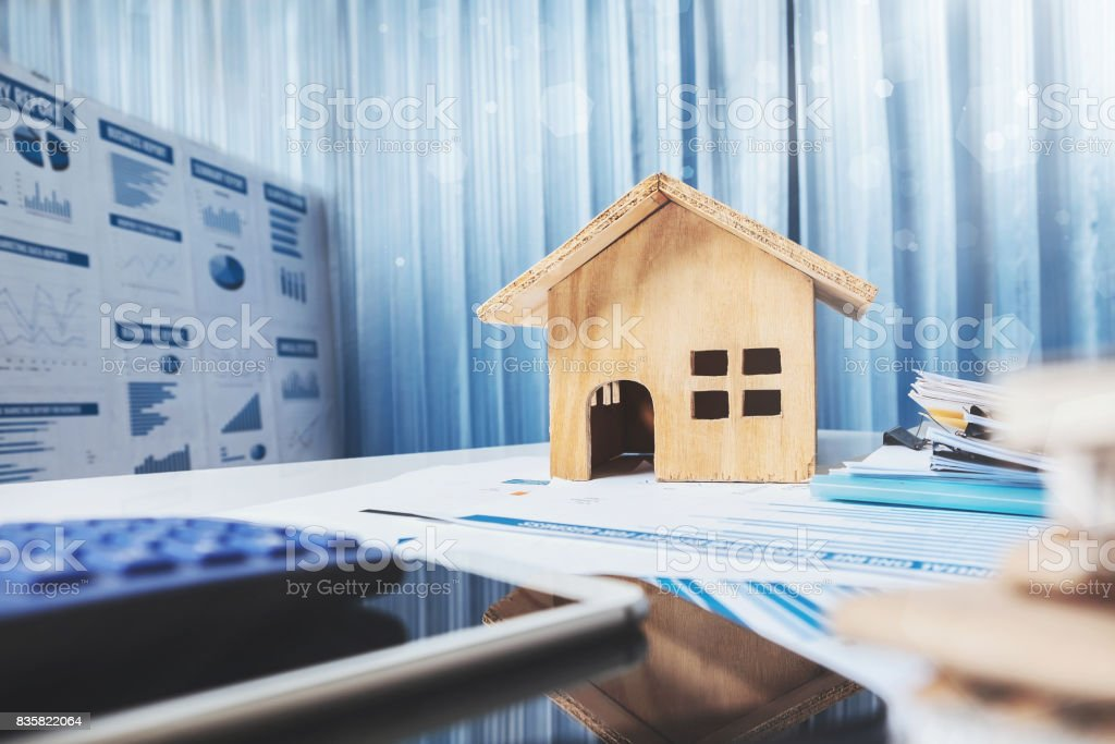 House and property for sale concept, wood house toy on office desk. stock photo