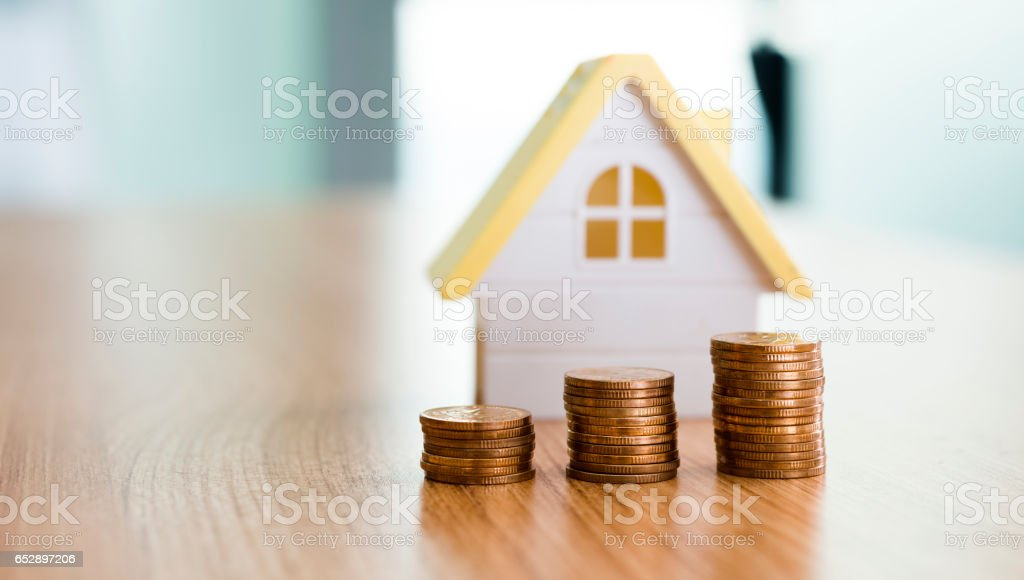 House and stacks of coins on table stock photo