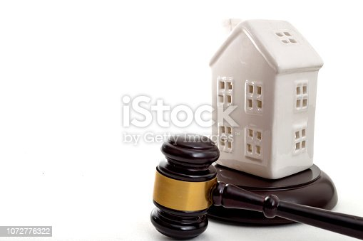 istock House Auction, property foreclosure and buying a new home concept with a white house model and a gavel isolated on white background with copyspace 1072776322