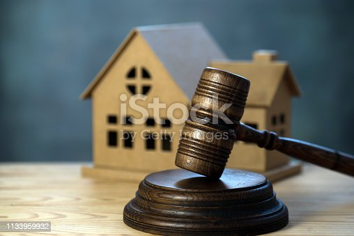 istock House auctions. A wooden hammer and a paper house 1133959932