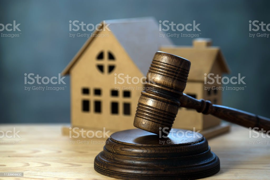 House auctions. A wooden hammer and a paper house stock photo