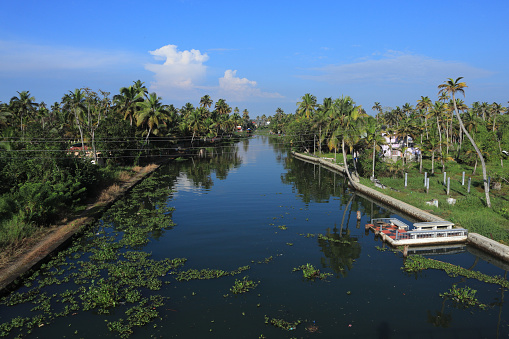 Alleppey, India - February 16,2021 : A traditional house boat cruising tourists across the backwaters in Alleppey, Kerala, India