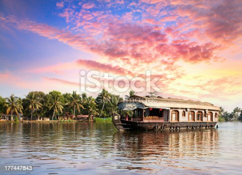 House boat in backwaters near palms at dramatic sunset sky in alappuzha, Kerala, India