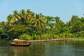 House boat in backwaters against palms background and blue sky In Alappey, Kerala, India. Kerala state, with a large network of inland canals earning it the sobriquet \