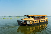 House boat in backwaters against  blue sky In Alappey, Kerala, India. Reflection of the boat in water. Kerala state, with a large network of inland canals earning it the sobriquet \