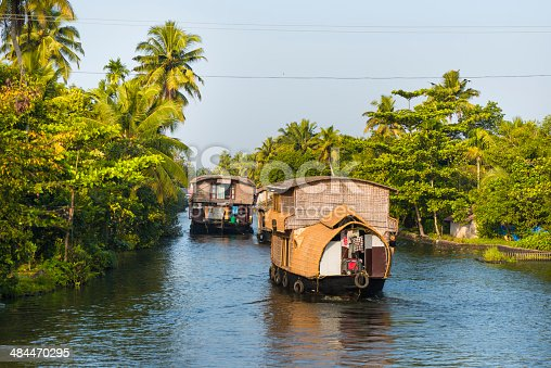 Many house boats sail down the river in backwaters against palms background and blue sky In Alappey, Kerala, India. Kerala state, with a large network of inland canals earning it the sobriquet