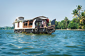 Alleppey - Alappuzha, India - 13 November 2017: House boat on the river of the Kerala backwaters with tropical palm trees