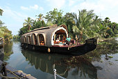 Alleppey - Alappuzha, India - 13 November 2017: House boats going back to the harbour on the river of the Kerala backwaters with tropical palm trees