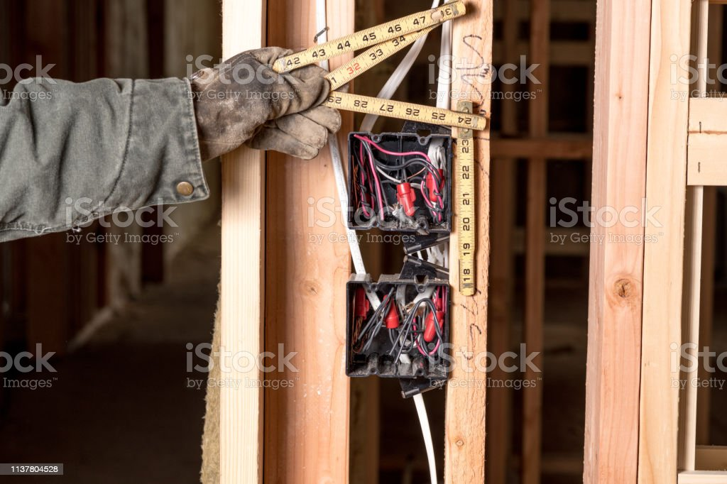 Space between studs is measured with a ruler by a construction worker