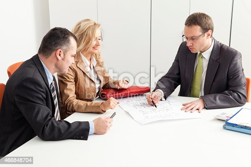 466848706 istock photo House buyers talking to a consultant at a desk 466848704