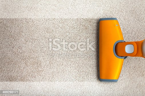 Senior woman cleaning carpet with red vacuum cleaner in the bedroom. Grandmother doing everyday chores and tasks, dusting, vacuuming, sweeping in the house.