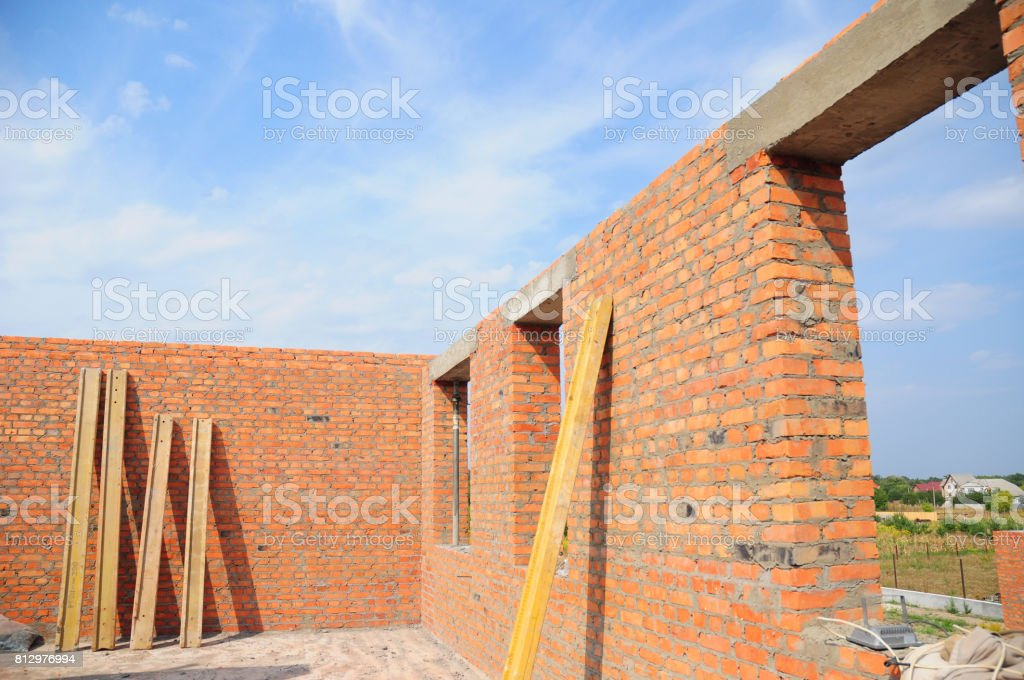House construction concept.  Interior of a unfinished red brick house under construction. Closeup on windows hole construction with concrete lintel. stock photo