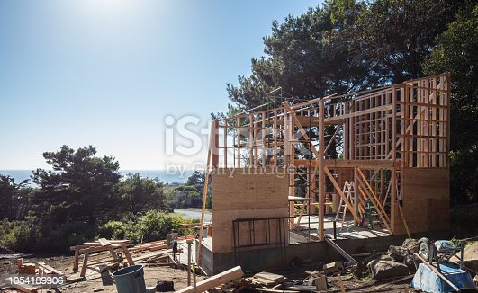 House construction framing in California by pacific ocean on sunny day