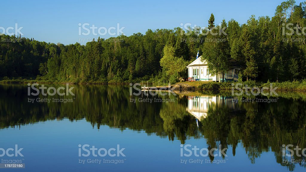 Rural home on a lake in the morning in Canada. The lake is quiet and...
