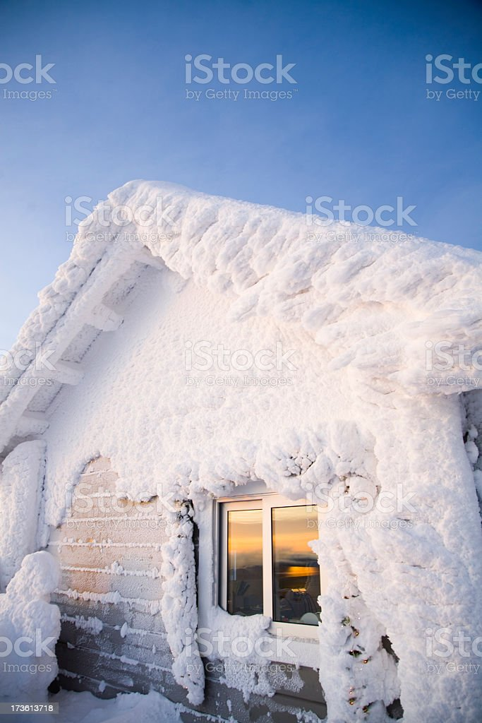 House covered in snow against a blue sky royalty-free stock photo